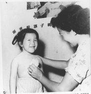 巨鹿路第三托儿所的阿姨给孩子擦粉之情形