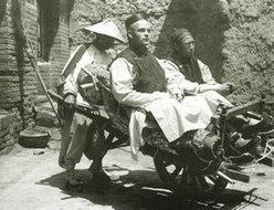 乘坐独轮车去乡下的传教士和他的助手